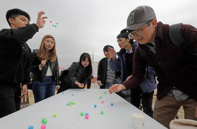 전통놀이 체험 부스에서 관람객들이 '공기놀이'를 즐기고 있다.