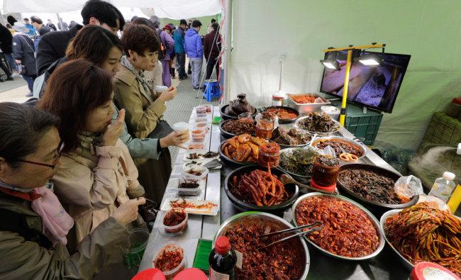 순창이조전통식품 부스에서 젓갈과 김치 등을 맛보는 사람들.