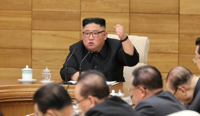 김정은 북한 국무위원장이 4월 9일 노동당 정치국 확대회의에서 왼 주먹을 불끈 쥐며 '자력갱생'을 강조하고 있다. [노동신문]