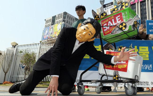 일본산 수산물 수입 대응 시민 네트워크가 4월 12일 서울 종로구 정부서울청사 앞에서 일본산 수산물 WTO 분쟁 승소와 관련해 퍼포먼스를 펼치고 있다. [뉴시스]