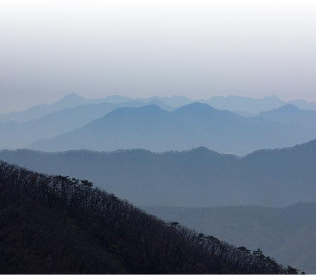 산의 정상부 뒤로 영남의 산세가 병풍처럼 펼쳐져 있다.