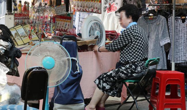 지난해 여름 서울 남대문시장에서 한 상인이 선풍기로 더위를 식히는 모습. [뉴스1]