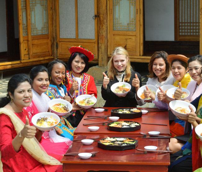 한옥마을을 방문한 해외 신자들은 가지각색 재료를 넣은 비빔밥을 완성해 들어 보이고 있다.