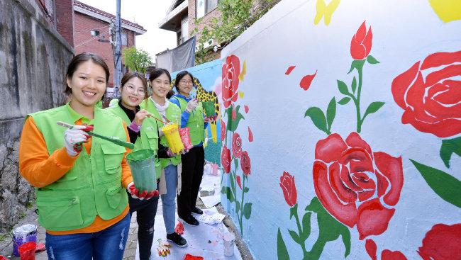 하나님의 교회 직장인청년봉사단 ASEZ WAO가 벽화 그리기 봉사를 진행하며 환하게 웃고 있다. 알록달록한 벽화가 눈에 띈다.