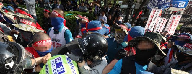 6월 22일 서울 종로구 현대 중공업 서울사무소 앞에서 열린 민주노총 금속노조 집회에서 한 경찰관이 집회 참가자들에 둘러싸여 끌려가고 있다. [뉴스1]