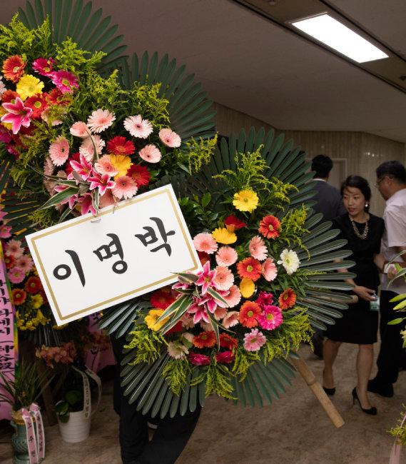 6월 10일 서울 여의도 국회도서관에서 열린 '평등의 역습' 북콘서트 행사장으로 이명박 전 대통령이 보낸 화환이 들어가고 있다. [박해윤 기자]