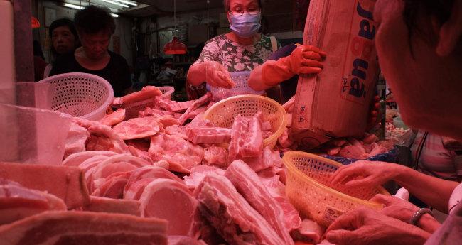5월 16일 홍콩에서 한 시민이 냉동 돼지고기를 구입하고 있다. 중국에서 수입한 돼지에서 돼지열병바이러스가 검출돼 홍콩도 비상이다. [뉴시스]