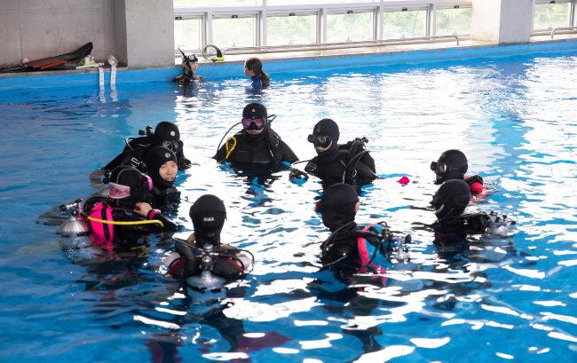 잠수 장비를 갖추고 수중훈련을 하는 사람들.