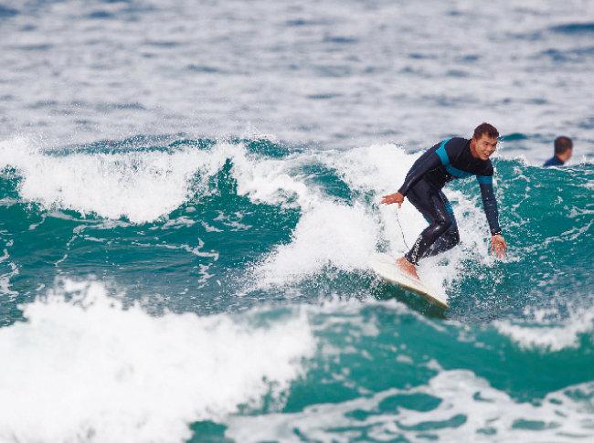 윤상욱 씨가 인구해수욕장에서 서핑을 즐기고 있다.