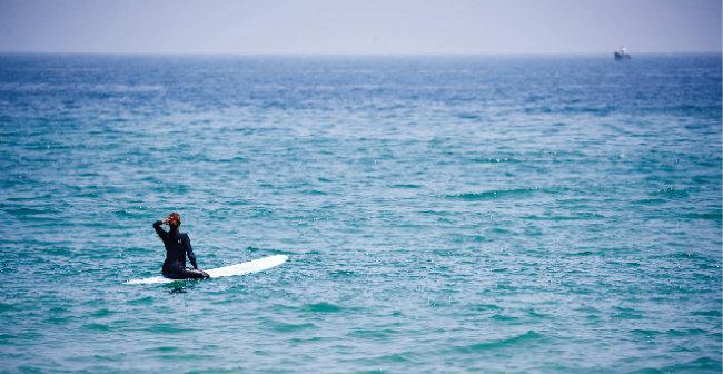 옥계면 옥계해변에서 한 여성이 서핑보드를 타고 파도를 기다리고 있다.