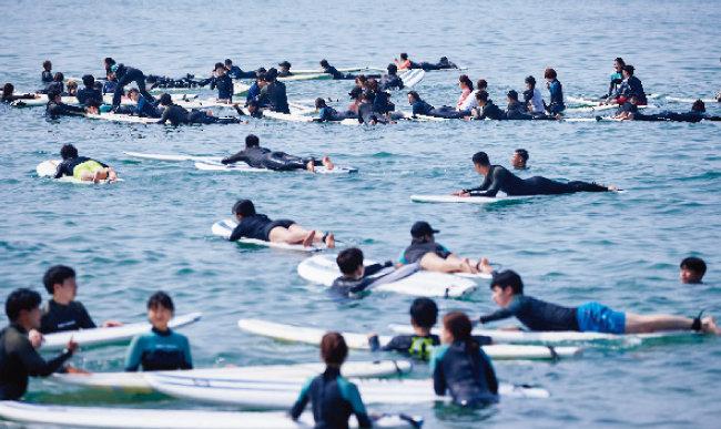 현북면 하조대해수욕장에서 서핑을 즐기는 사람들.