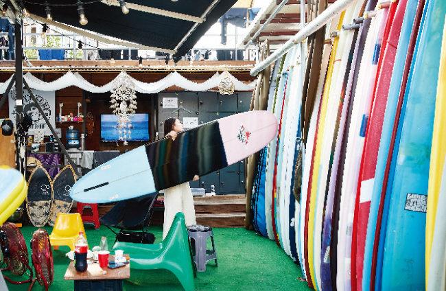 한 여성이 서핑 용품 가게에 서핑보드를 보관하고 있다.