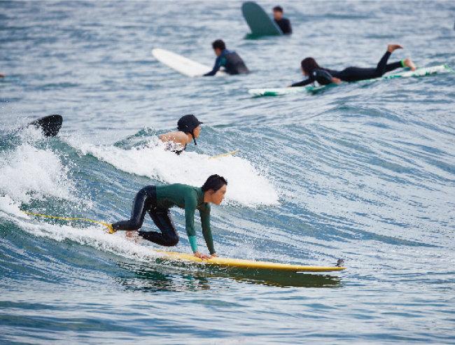 한 여성이 서핑보드에서 일어서기 위해 균형을 잡고 있다.