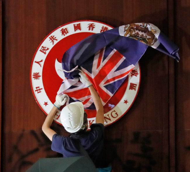 7월 1일 홍콩 입법원을 장악한 '범죄인 인도법안' 반대 시위대가 벽에 걸린 홍콩 로고 위에 과거 홍콩 식민지 깃발을 덮고 있다. [AP=뉴시스]