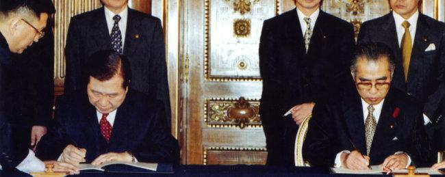 1998년 10월 8일 김대중 당시 대통령(왼쪽)과 오부치 게이조 당시 일본 총리가 도쿄에서 '21세기 새 시대를 위한 공동선언'에 서명하고 있다. [동아일보]