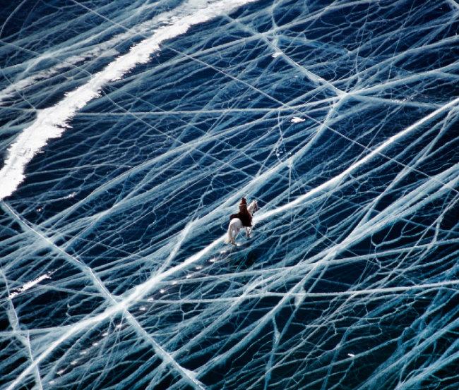 러시아 시베리아 남동쪽에 위치한 바이칼호를 건너는 말과 기수.