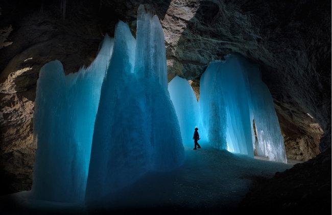 오스트리아 베르펜벵 근처에 있는 얼음 동굴 아이스코겔홀레에서 우뚝 솟은 얼음 기둥을 올려다보고 있는 한 탐험가의 모습을 담았다.