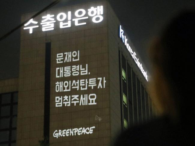 6월 30일 오후 서울 영등포구 여의도 공원 인근에서 국제환경단체 그린피스 관계자들이 정부의 해외 석탄 투자 중단 촉구 메시지를 담은 레이저 빔을 한국수출입은행 건물에 투사하고 있다. [뉴시스]