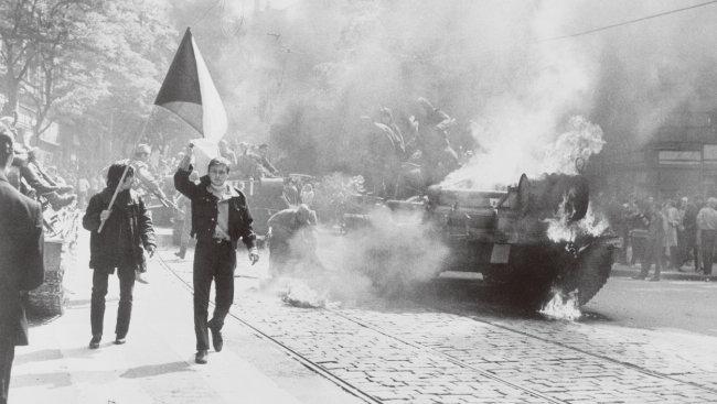 프라하의 봄이 시작된 1968년 소련이 체코슬로바키아를 침공하는 동안, 프라하에서 체코슬로바키아인이 불타는 탱크 옆으로 국기를 흔들고 있다. [The Central Intelligence Agency]