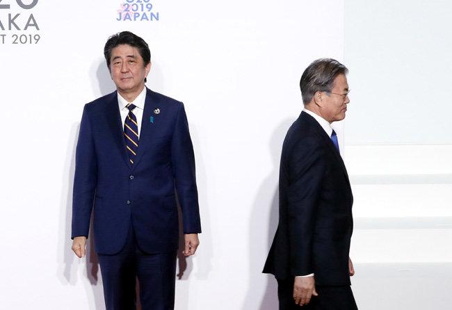 문재인 대통령이 6월 28일 일본 인텍스 오사카에서 열린 G20 정상회의 공식 환영식에서 의장국인 일본 아베 신조 총리와 인사한 뒤 이동하고 있다. [청와대 사진기자단]