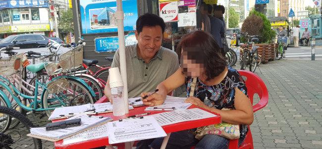 오세훈 전 서울시장이 서울 광진구 거리에서 한국당 당원 모집 활동을 하고 있다. 한 시민이 오 전 시장의 권유로 입 당원서를 쓰는 모습.