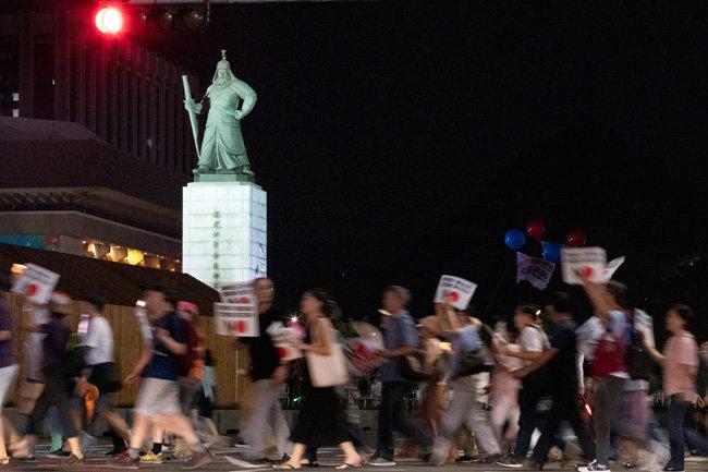 월 3일 아베 신조 일본 총리를 규탄하는 촛불 집회에 참석한 참가자들이 서울 광화문광장을 가로질러 행진하고 있다. 충무공 이순신이 이 행렬을 내려다보고 있다.