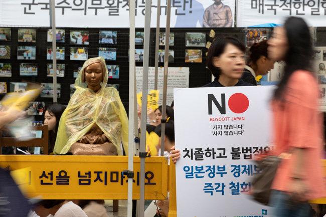 일본군 위안부 피해자를 기리는 평화의 소녀상 앞에서 한 시민이 '보이콧' 재팬 피켓을 들고 있다.