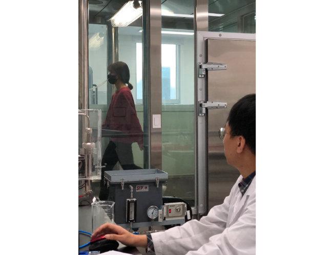 마스크 착용자가 체임버에 들어가 누설률 시험을 하는 모습. [한국의류시험연구원 제공]
