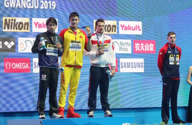 2019 광주세계수영선수권대회 남자 자유형 200m 결승 시상식, 금메달을 획득한 중국의 쑨양(왼쪽에서 두 번째)이 다른 메달리스트들과 기념촬영을 하는 가운데 함께 동메달을 획득한 영국의 던컨 스콧(오른쪽)이 멀리 서 있다. [뉴시스]