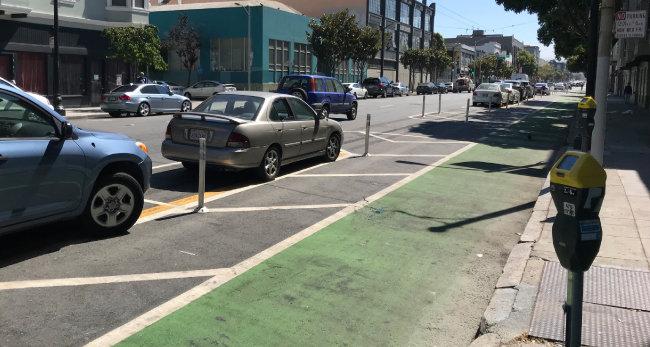 3월 자전거 운전자 사망사고 이후 샌프란시스코 교차로 주변에 설치된 자전거 보호도로. 차량 진행 방향 기준으로 맨 오른쪽이 녹색으로 칠해진 자전거 보호도로다. 자전거도로와 일정한 간격을 두고 왼쪽에 마련된 노상주차장에 자동차들이 일렬로 주차돼 있다. 이 주차장 왼쪽이 차도다.
