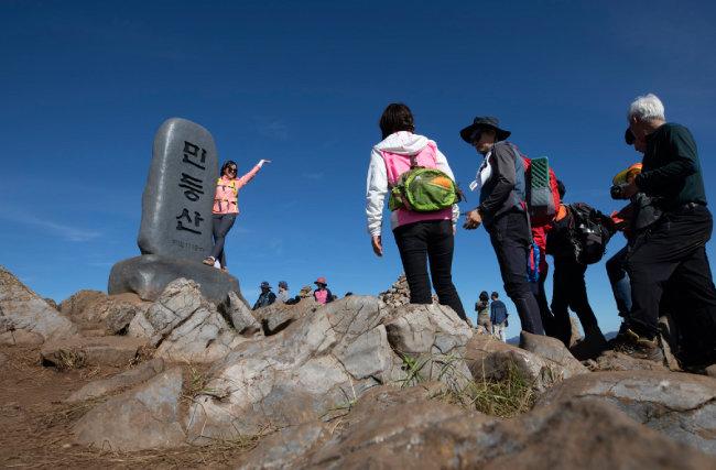 민둥산이란 글씨가 아로새겨진 정상 표지석 주위로 사람들이 모여든다.