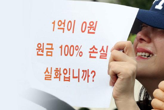 DLF 투자 피해자가 9월 27일 서울 여의도 국회 앞에서 해당 은행 국정조사를 요구하며 손팻말을 들고 있다. [뉴시스]
