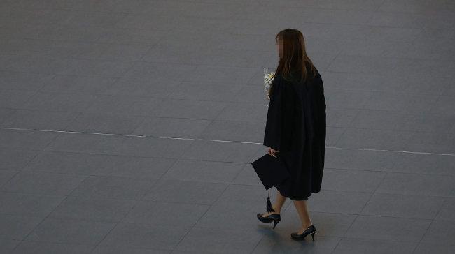 한 사립대 졸업식에서 한 학생이 졸업 가운을 입은 채 꽃다발과 학사모를 들고 어디론가 걸어가고 있다. [동아DB]
