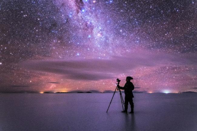 볼리비아 우유니 사막에 선 김상구 작가가 찬란한 별빛에 둘러싸여 있다.