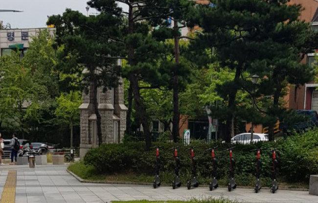 서울시 한 대학교 강의동 앞에  주차된 전동킥보드들.