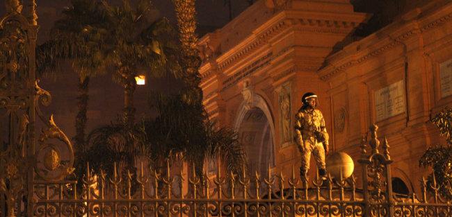 """2011년 1월 29일 이집트 카이로에 있는 이집트 국립박물관에서 한 병사가 경계를 서고 있다. 앞서 이집트 문화재위원회는 """"박물관에 침입해 유물을 훔치려 한 범인 9명이 체포됐다""""고 밝혔다. [뉴시스]"""