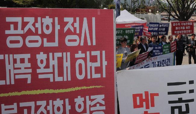 학생부종합전형 확대를 요구하는 교육단체와 정시 확대를 요구하는 단체가 2018년 4월 25일 서울 종로구 세종로 정부서울청사 정문에서 서로 마주 보며 피켓을 들고 있다. [원대연 동아일보 기자]