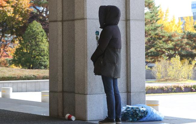 조국 전 법무부 장관이 피의자 신분으로 검찰에 출석한 11월 14일, 지지자 한 명이 파란색 장미를 들고 서울 서초동 서울중앙지검 입구에 서 있다. 파란색 장미의 꽃말은 '기적' '희망' '포기하지 않는 사랑'이다.  [뉴스1]