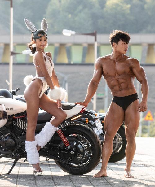 행사장 밖에서 남녀 선수가 오토바이를 배경으로 포즈를 취하고 있다.