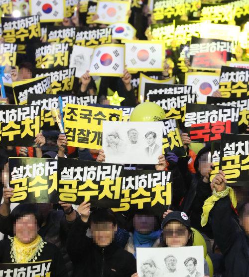 11월 2일 서울 여의도공원 인근에서 열린 '제12차 검찰개혁·공수처 설치 촛불 문화제'에 참가한 시민들이 '설치하라 공수처' 등이 쓰인 손팻말을 들어 보이고 있다. [뉴시스]