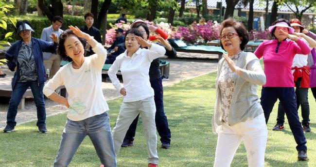 2016년 4월 29일 서울 광진구 어린이대공원 잔디밭에서 열린 '어르신 야외 체력관리 교실'에 참가한 60세 이상 참가자들이 전담 지도자의 동작을 보고 체조를 따라하고 있다. [김경제 동아일보 기자]
