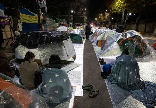 밤이 되면 청와대 앞길은 텐트촌으로 변모한다. 벽을 사이에 두고 대한민국 최고 권력자와 좌우 단체 투쟁가들이 함께 잠을 청한다.