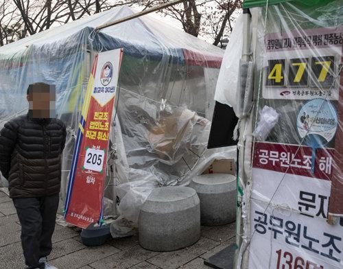 진보단체('전국교원노조'와 '공무원노조')의 농성 천막 앞으로 '전교조 법외노조 직권취소 노숙 205일차'라는 문구가 보인다.