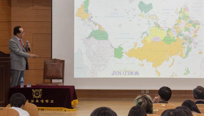 김재철 동원그룹 명예회장이 세계지도를 거꾸로 돌려 보여주며 우리나라의 입지적 장점을 설명하고 있다. [박해윤 기자]