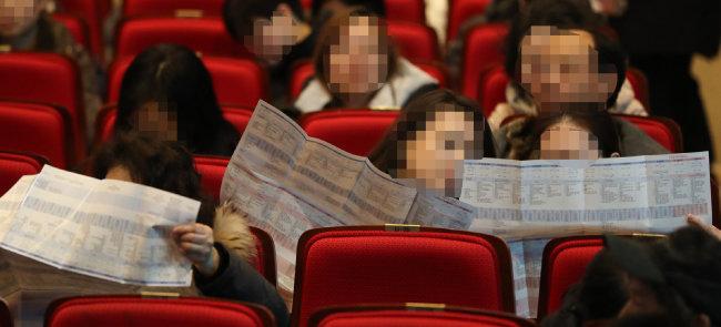 2019년 12월 10일 서울 노원구 광운대에서 열린 2020 대입 정시전형 대비 진학설명회에서 수험생 학부모들이 배치표를 살펴보고 있다. [뉴스1]