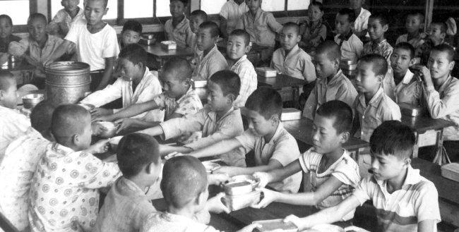 1960년대 초등학교 풍경. 학생들이 도시락을 싸오지 못한 친구에게 도시락을 건네주고 있다. [동아DB]