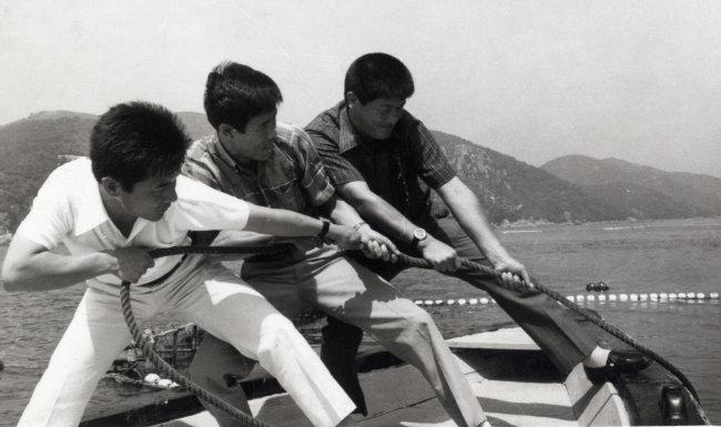 1973년 6월 경남 통영 앞바다에서 밀수단속반원이 어장 근처 바다에 숨겨둔 밀수품을 적발해 끌어 올리고 있다. [동아DB]