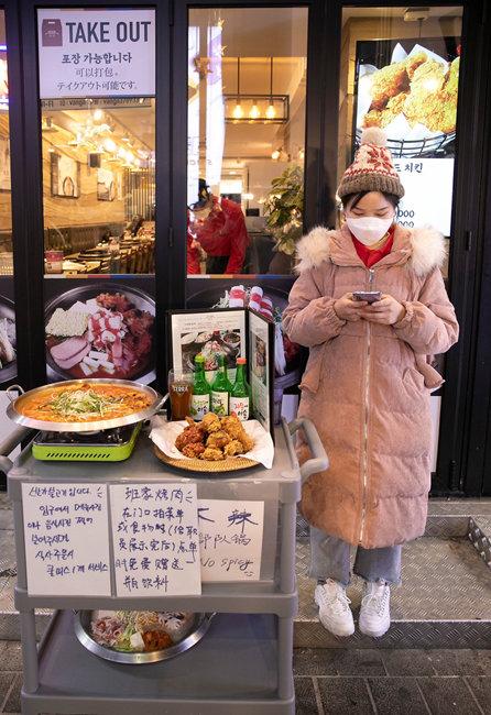 음식점 앞에서 관광객을 호객하는 직원