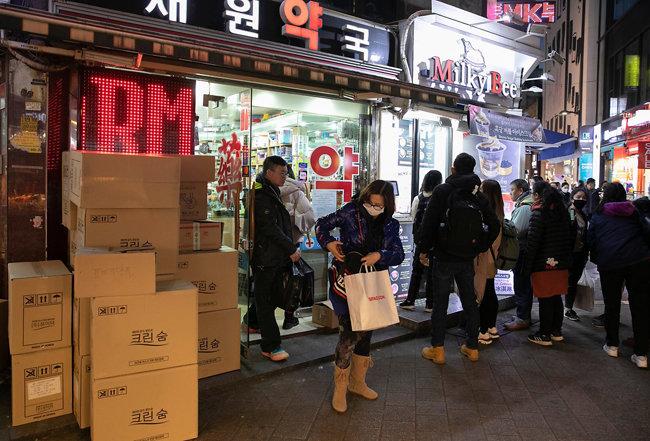 약국 앞에 마스크 박스가 놓인 채 줄을 선 관광객들