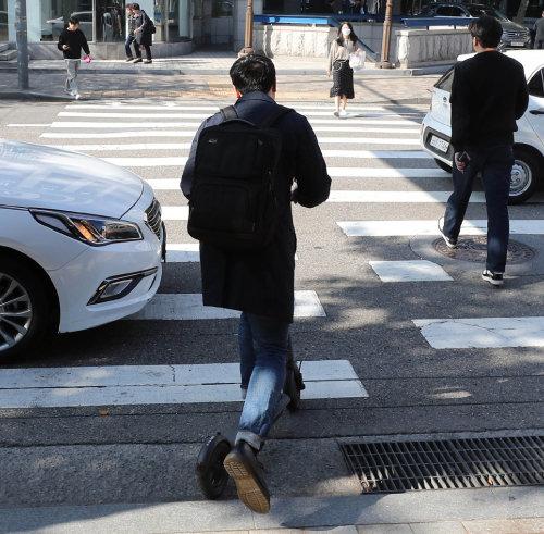 서울 강남구 역삼초교 사거리에서 전동킥보드 이용자가 횡단보도와 인도를 이용해 이동하고 있다. 도로교통법상 전동킥보드는 인도로 주행할 수 없다. [동아DB]